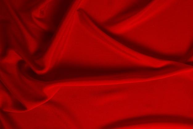 Tekstura luksusowej tkaniny z czerwonego jedwabiu lub satyny może służyć jako abstrakcyjna powierzchnia