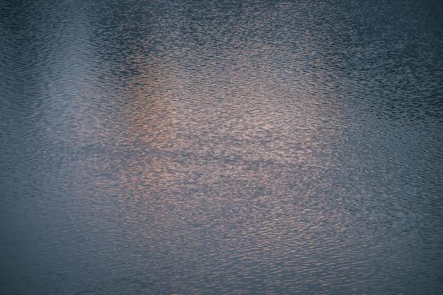 Tekstura magenta spokojne wody jeziora o wschodzie słońca. medytacyjne fale na powierzchni wody. natura minimalne tło różowego jeziora o zachodzie słońca. naturalne tło czystej wody. pełna klatka fragmentu jeziora.
