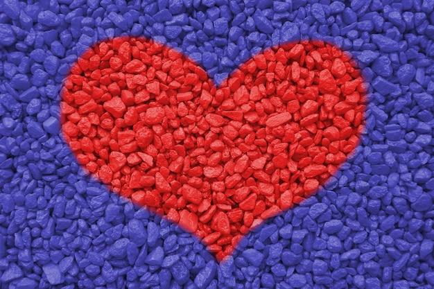 Tekstura małych ozdobnych kamieni czerwone serce na niebieskim tle pojęcie miłości i walentynki