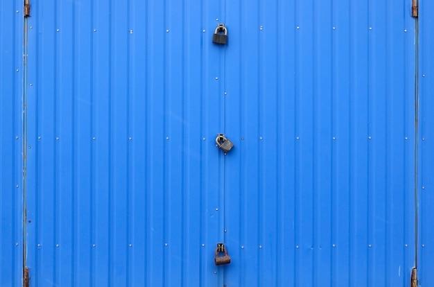 Tekstura metalowej niebieskiej ściany z zamkniętą bramą na trzy zamki