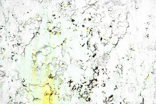 Tekstura metalowej ściany z pęknięciami i zadrapaniami, które mogą służyć jako tło