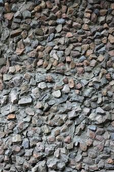 Tekstura mocnej kamiennej ściany wielu betonowanych kamieni o różnych kształtach