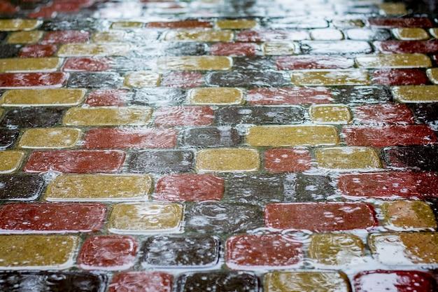 Tekstura mokrych płytek chodnikowych z odblaskiem