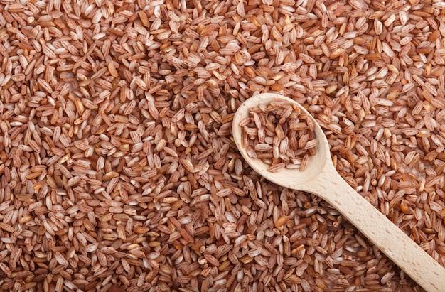 Tekstura nieoszlifowany brązowy ryż z drewnianą łyżką. widok z góry, z bliska.