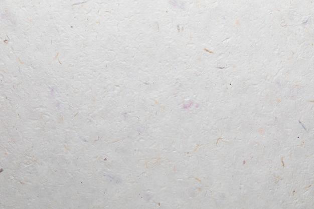 Tekstura papieru czerpanego z materiałów pochodzących z recyklingu, kolorowych włókien bawełny i liści drzewa. w delikatnych odcieniach, różowym, fioletowym, fioletowym, żółtym, pomarańczowym, niebieskim i waniliowym.