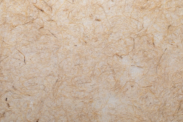 Tekstura papieru czerpanego z włóknami roślinnymi, takimi jak słoma. w delikatnych odcieniach, żółci, pomarańczy, brązów i wanilii.