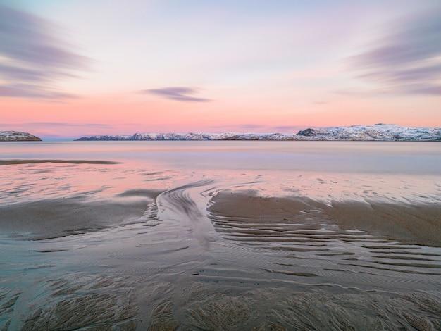 Tekstura piasku na plaży w czasie odpływu o zachodzie słońca