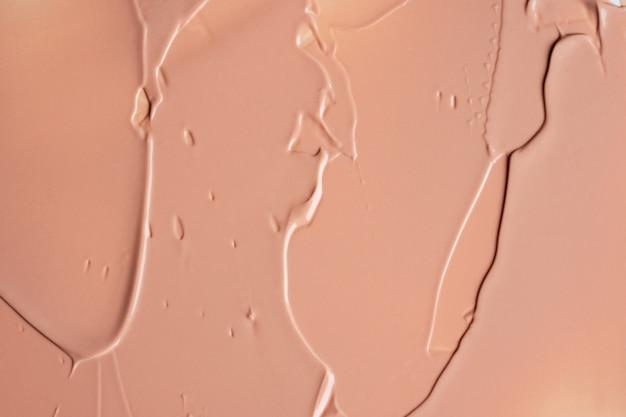 Tekstura płynnego beżowego podkładu rozmycie kremowe tło makijażu. rozmazy akrylowe.
