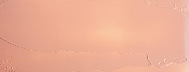 Tekstura płynnego beżowego podkładu rozmycie kremowe tło makijażu. szeroki baner.