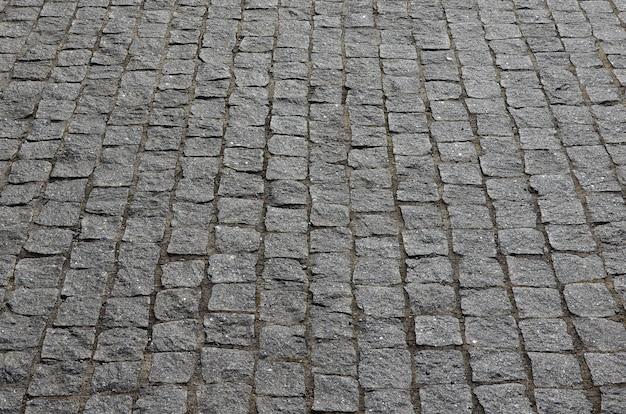 Tekstura płyty chodnikowej (kostki brukowej) wielu małych kamieni o kwadratowym kształcie w jasnym świetle słonecznym