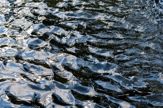 Tekstura pofałdowanej ciemnej powierzchni wody z pasemkami