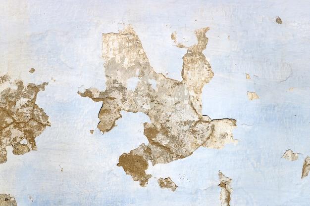 Tekstura pomalowany na niebiesko stary wyblakły betonowy mur z łuszczącą się farbą. abstrakcyjne tło