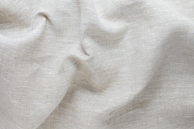 Tekstura pomarszczonej, pogniecionej naturalnej tkaniny lnianej z bliska szarego koloru.