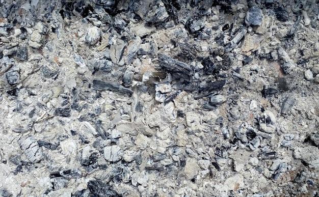 Tekstura popiołu pozostawionego po pożarze na szarych węglach przy ognisku