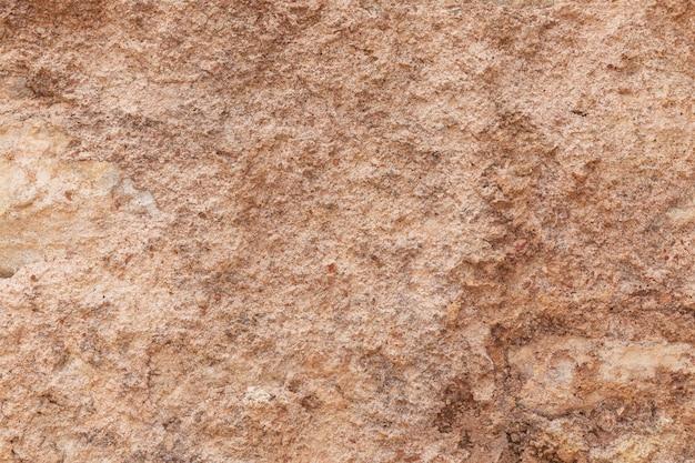 Tekstura powierzchni kamienia naturalnego, zbliżenie. materiał budowlany starożytnych cywilizacji. tło. miejsca na tekst.
