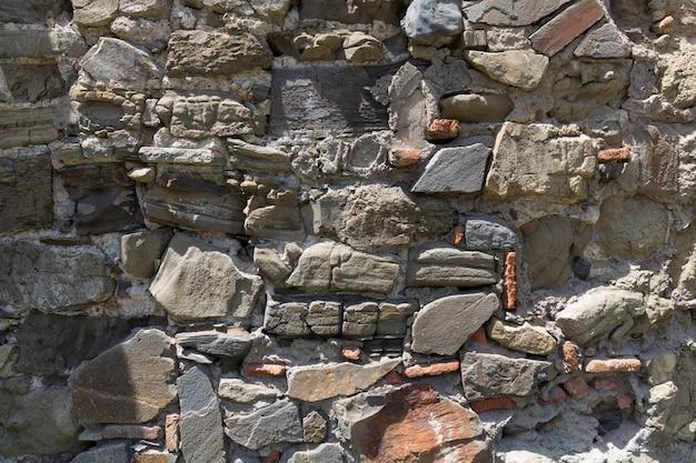 Tekstura ścian ze starych surowych cegieł i kamienia. stare mury zniszczone przez czas. zdjęcie wysokiej jakości