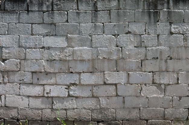 Tekstura ściana z cegieł z reliefowymi kamieniami w jaskrawym świetle słonecznym