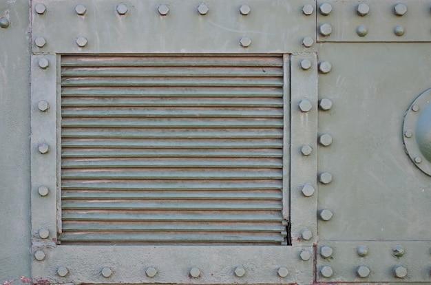 Tekstura ściany zbiornika, wykonana z metalu i wzmocniona wieloma śrubami i nitami.