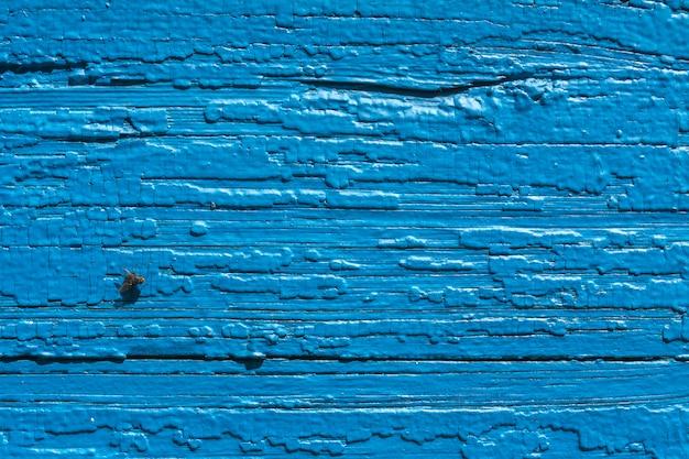 Tekstura. stara malująca ściana dom. stary drewniany płot. niebieska farba. leć na pokładzie.