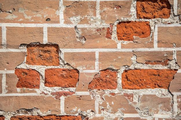 Tekstura starego czerwonego zniszczonego muru z cegły