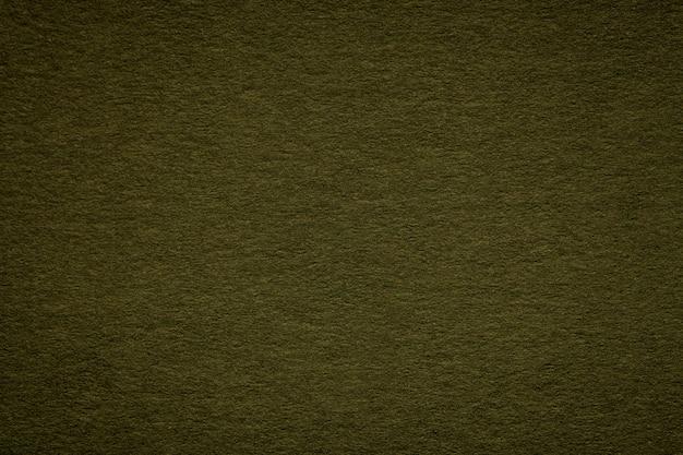 Tekstura starego zielonego papieru zbliżenie, struktura gęstego kartonu, czarne tło,