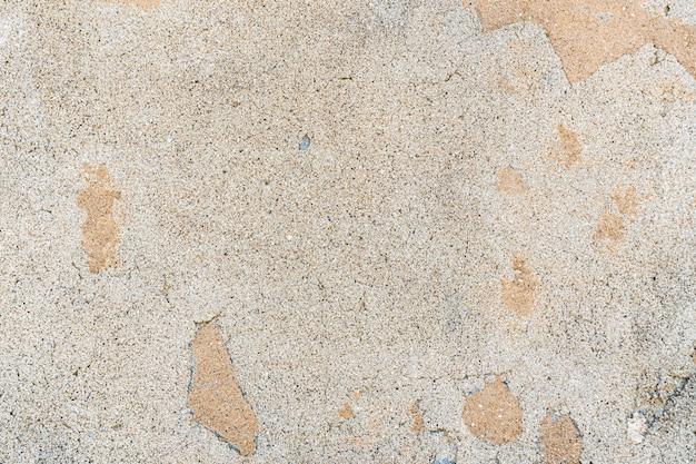 Tekstura starej betonowej ściany z zadrapaniami, pęknięciami, kurzem, szczelinami, szorstkością, sztukaterią. może służyć jako plakat lub tło do projektowania. skopiuj miejsce na wiadomość tekstową.