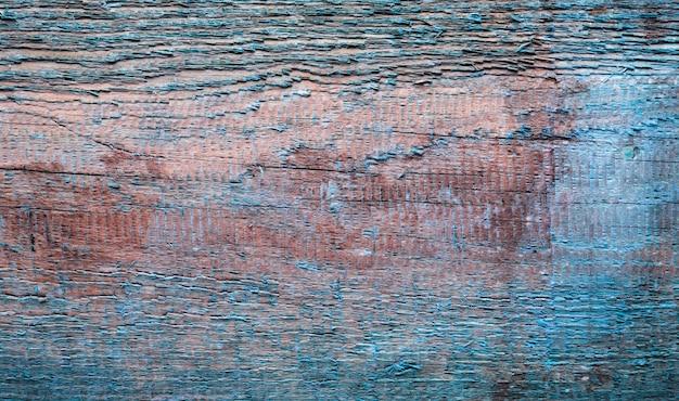 Tekstura starej deski z łuszczącą się niebieską farbą.