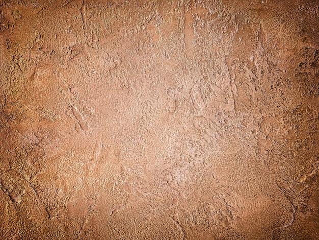 Tekstura starej ściany z dekoracyjnym tynkiem brązowym.