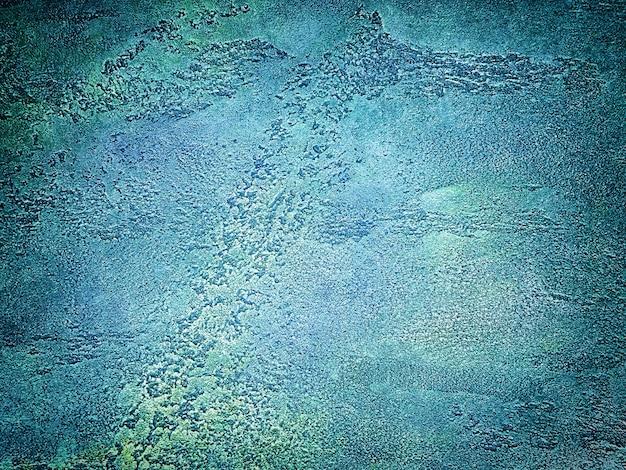 Tekstura starej ściany z dekoracyjnym tynkiem w kolorach niebieskim i zielonym