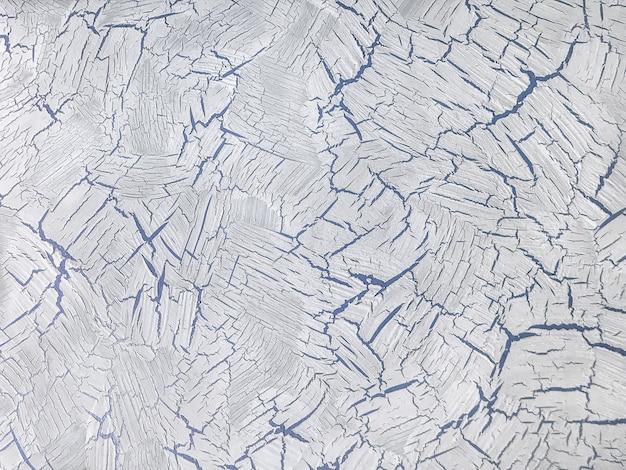 Tekstura starej ściany z tynkiem dekoracyjnym w kolorach białym i niebieskim.