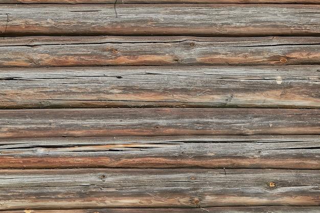 Tekstura starej wyblakłej ściany z bali z pęknięciami.