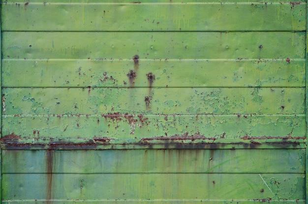 Tekstura starej zielonej metalowej ściany z poważnymi uszkodzeniami wynikającymi z narażenia na niekorzystne warunki pogodowe i wilgoć