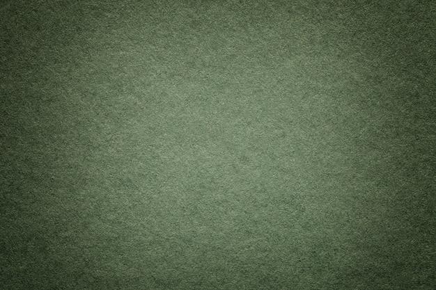 Tekstura stary ciemnozielony papierowy tło, zbliżenie. struktura gęstego głębokiego niebieskawego kartonu.