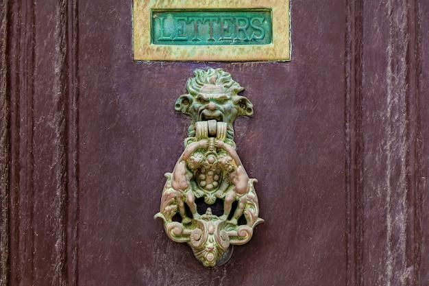 Tekstura starych drewnianych drewnianych drzwi z niezwykłymi metalowymi uchwytami na wyspie malta