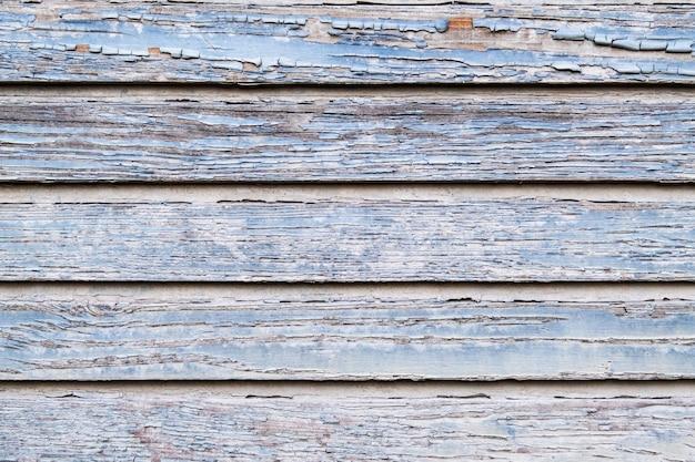 Tekstura starych odrapanych desek drewnianych z pękniętą niebieską farbą. tło z otworami węzłów.