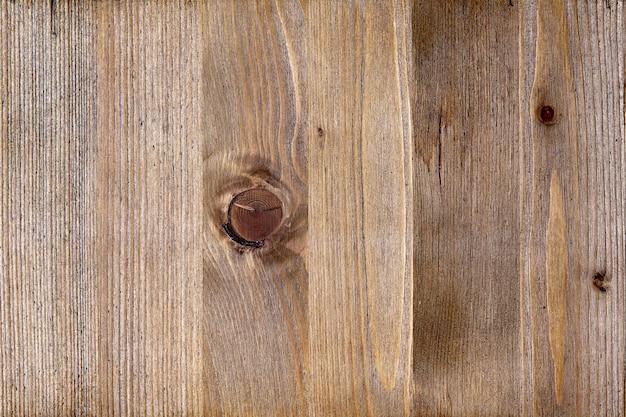 Tekstura stonowanej brązowej powierzchni drewna z sękami