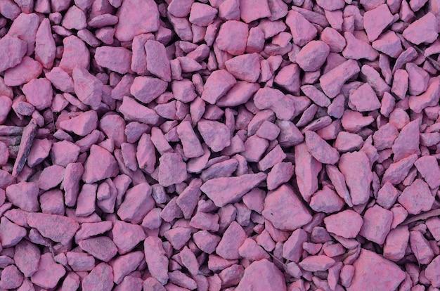 Tekstura stosu kruszonych kamieni, pomalowana na różowo