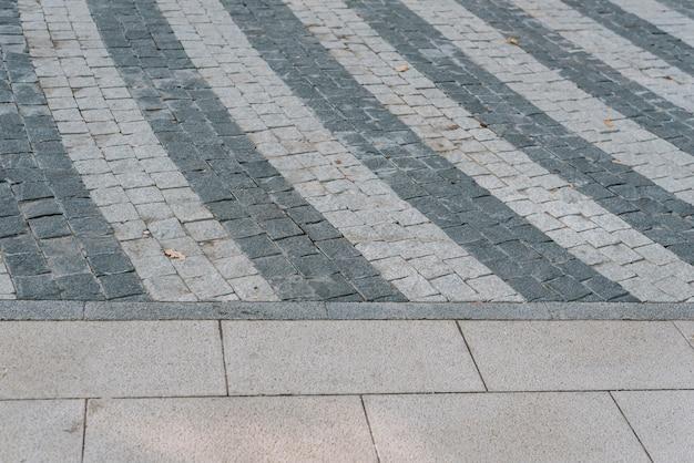Tekstura szarego kamienia kostki brukowej w zbliżeniu