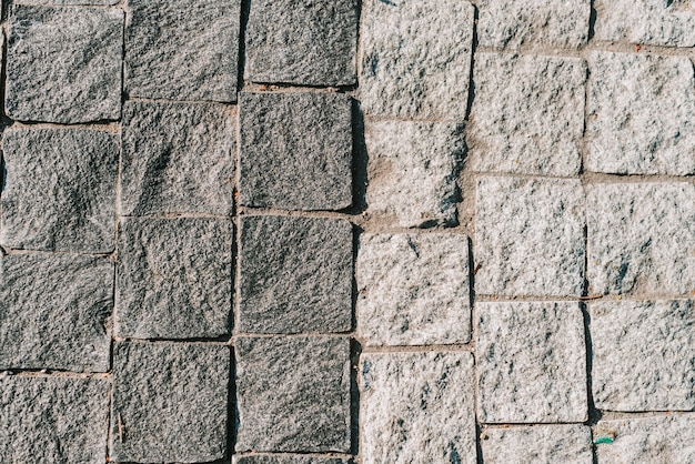 Tekstura szarej kamiennej kostki brukowej