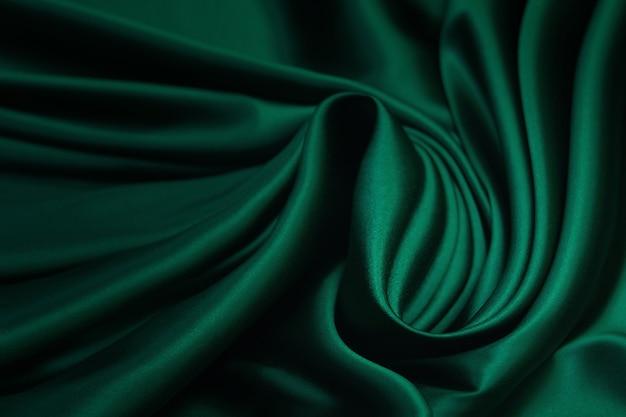 Tekstura, tekstura zielonej jedwabnej tkaniny. piękna szmaragdowo-zielona miękka tkanina jedwabna.