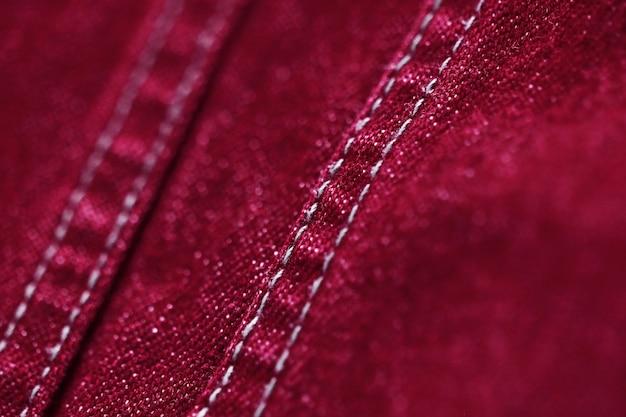 Tekstura tekstylna z czerwonej tkaniny z bliska, skup się tylko na jednym punkcie, miękkie tło blured