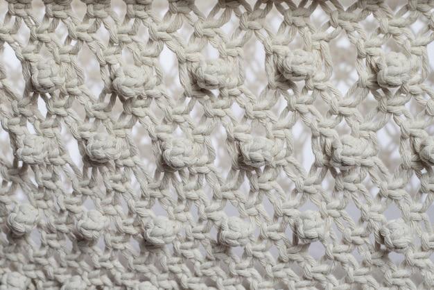 Tekstura tkana w stylu makramy z białych naturalnych nici bawełnianych.