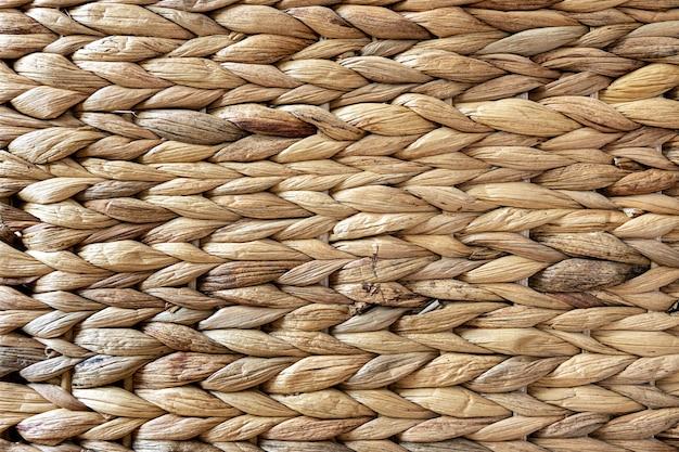 Tekstura tkanej beżowej słomy, tło warkoczy z bliska łodygi roślin.