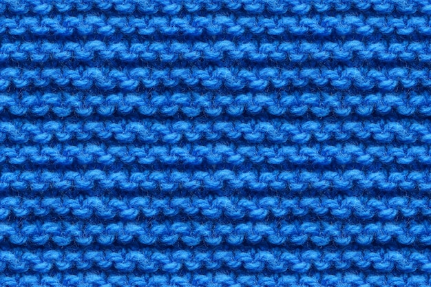 Tekstura tkaniny dzianiny niebieski. dziewiarska migawka makro tekstury. granatowa dzianina