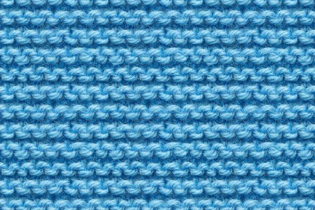 Tekstura tkaniny dzianiny niebieski. dziewiarska migawka makro tekstury. niebieska dzianina