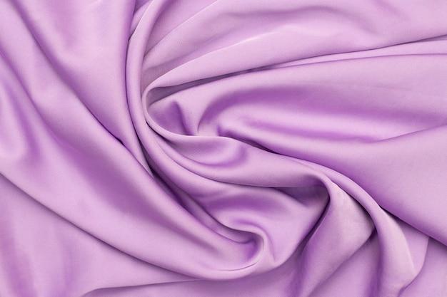 Tekstura tkaniny jedwabnej w kolorze liliowym. piękny luksus. skręcona gładka elegancka tkanina.