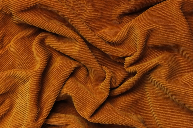 Tekstura tkaniny popsutymi pomarańczowy sztruks. zmięte tło