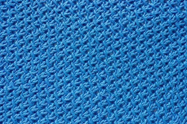 Tekstura tkaniny wiązanej niebieską przędzą.
