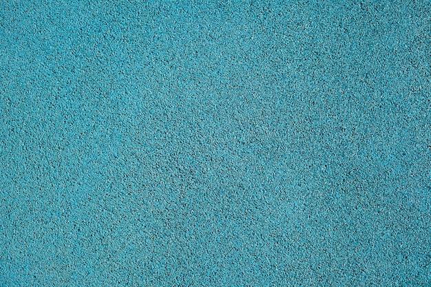 Tekstura tła niebieskiej okruchów gumy używanej do torów sportowych i placów zabaw dla dzieci