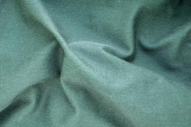 Tekstura tła to zielona miękka falista tkanina, widok z góry, zbliżenie.
